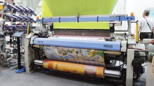 Stäubli demonstrated the capability of its jacquard weaving machines by producing intricately woven jacquard fabrics with a Barcelona-themed design.